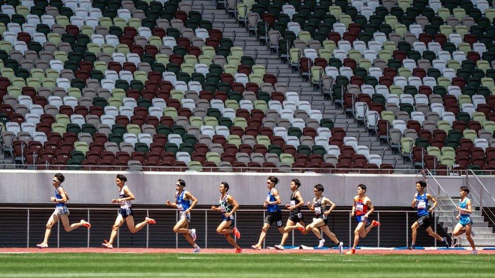 Athletes running through a stadium.